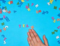 女性手和英语字母表的多彩多姿的木信件 库存照片