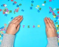 女性手和英语字母表的多彩多姿的木信件 库存图片