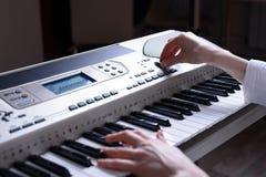 女性手在一架电子钢琴,背面图设定并且使用 免版税图库摄影
