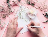 女性手在与花的信封写在桃红色桌背景 婚礼,邀请,情人节,母亲节问候 免版税库存图片