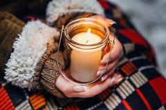 女性手在关闭温暖的冬天举灼烧的蜡烛 免版税库存照片