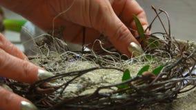 女性手在复活节巢投入西沙尔麻和绿色枝杈 股票视频