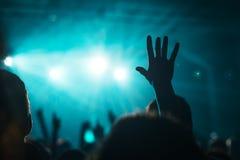 女性手在摇滚乐音乐会的天空中上升了 免版税图库摄影