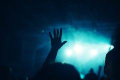 女性手在摇滚乐音乐会的天空中上升了 免版税库存照片