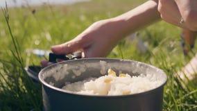 女性手在虚构以后投入热的粥在野营的关闭 影视素材