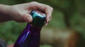 女性手在青苔隐蔽的森林里松开紫罗兰色瓶的盒盖在特写镜头的 影视素材