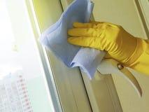 女性手在黄色与一块蓝色旧布玻璃的手套国内家庭洗衣机房子窗口里 免版税图库摄影