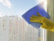 女性手在黄色与一块蓝色旧布玻璃的手套国内洗衣机房子窗口里 库存图片
