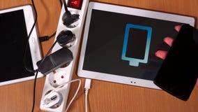 女性手塞住片剂计算机和电话对充电器在引伸插口 股票录像