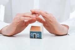 女性手守卫一个玩具房子 免版税库存照片