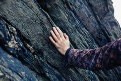 年轻女性手感人的岩石 图库摄影