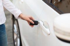 女性手打开在自动的关键系统的白色汽车 库存图片