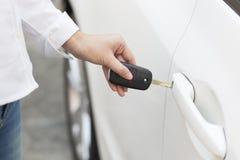 女性手打开在自动的关键系统的白色汽车 免版税库存照片