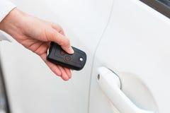 女性手打开在自动的关键系统的白色汽车 图库摄影