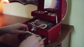 女性手打开首饰的红色箱子,并且采取在箱子珍珠外面成串珠状 股票视频