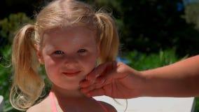 女性手抹上在女孩的面孔的奶油 股票视频