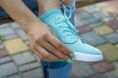 女性手抹布料穿上鞋子户外 库存照片