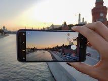 女性手拍在您的智能手机城市日落的一张照片 免版税图库摄影