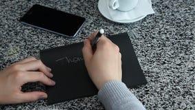 女性手拼写感谢您在黑纸放置的桌上 股票视频