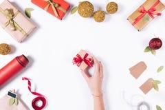 女性手拾起有礼物的一个小盒子 免版税库存图片