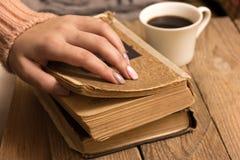 女性手拿着一个咖啡杯和一本老开放书 库存照片