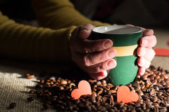 女性手拿着一个咖啡杯用豆 免版税库存照片