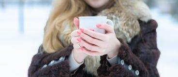 女性手拿着一个白色杯子 库存图片