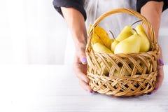 女性手拿着一个篮子用梨 库存照片