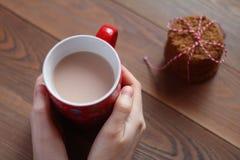 女性手拿着一个红色杯子在木桌上的可可粉 库存照片