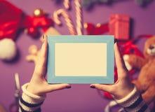 女性手拿着一个蓝色照片框架 免版税图库摄影