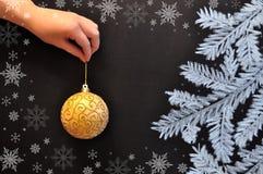 女性手拿着圣诞节球以黑板为背景 免版税库存图片
