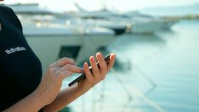 女性手拿着在口岸被弄脏的背景的智能手机与游艇的 图库摄影