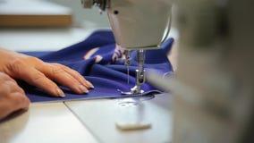 女性手拿着在缝纫机后的布料 在缝纫机后的裁缝,裁缝在工作, 股票录像
