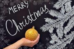 女性手拿着在黑板的圣诞节球 图库摄影