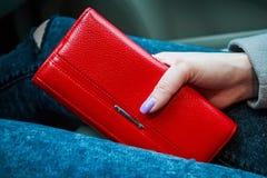 女性手拿着妇女的现代红色金钱钱包 库存图片