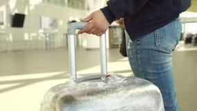 女性手拿着手提箱把柄,当站在队中在机场时 股票视频