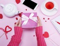 女性手拿着有一把桃红色弓的被包装的箱子 免版税图库摄影