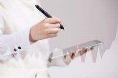 女性手拿着铁笔和与图表图一起使用 busines的,股市概念未来技术 库存照片