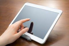 女性手指接触在一个持有人的一种空白的白色企业片剂在书桌上 免版税库存照片