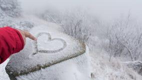 女性手指画好运的符号心脏在雪 免版税图库摄影