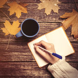 女性手文字某事在咖啡的笔记本附近 库存图片