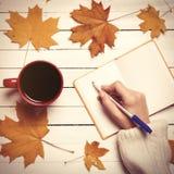 女性手文字某事在咖啡的笔记本附近 免版税库存照片
