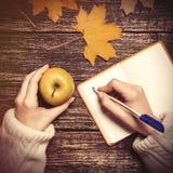 女性手文字某事对笔记本和藏品苹果 库存照片