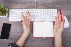 女性手文字特写镜头在一个笔记本的在企业书桌上 免版税库存照片