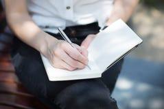女性手文字的特写镜头在一个空白的笔记本的有笔的 免版税库存图片