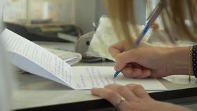 女性手文字的特写镜头在一个空白的笔记本的有笔的 女性手文字的特写镜头在一个空白的笔记本的 股票录像