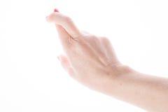 女性手显示在白色的好运标志 图库摄影