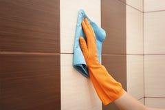 女性手清洁铺磁砖了墙壁 免版税图库摄影