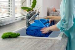 女性手特写镜头在厨房水槽的水的压力下漂洗蓝色板材在窗口前面 免版税库存图片