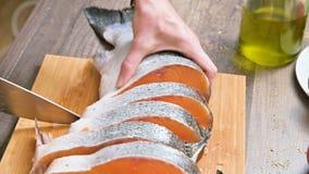女性手特写镜头用刀子切开在一张木桌上的一条大三文鱼家庭烹饪 影视素材
